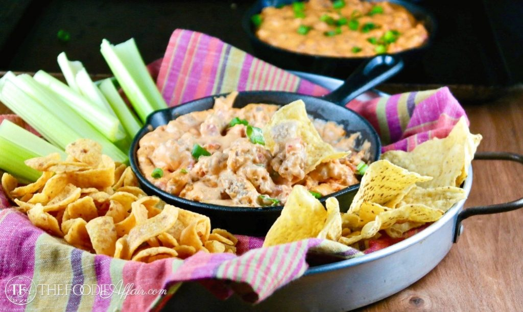 Appetizer tray with chips and celery sticks surrounded by a iron skillet of sausage queso dip #EasyRecipe #appetizer #Dip | www.thefoodieaffair.com