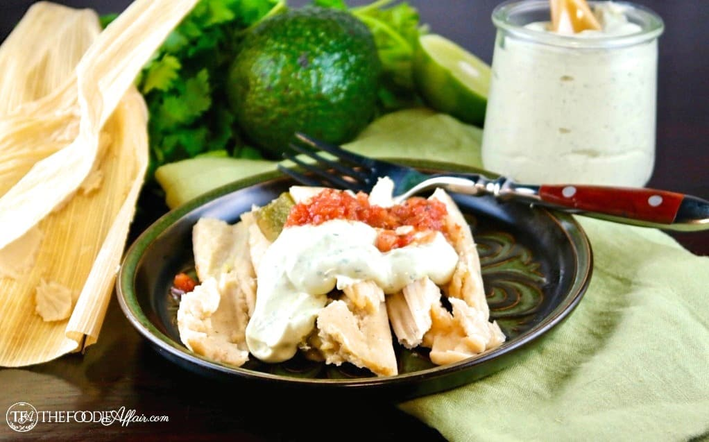 A blue place with tamales topped with avocado cream sauce and salsa #avocado #sauce #keto | www.thefoodieaffair.com
