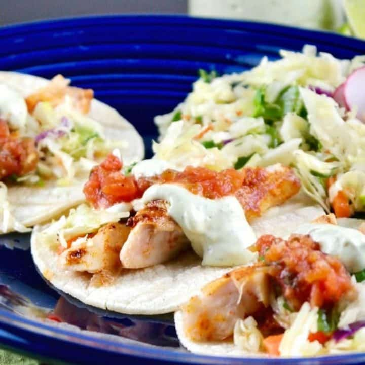 Healthy Fish Tacos recipe with fresh caught cod topped with salsa, avocado cream and slaw.