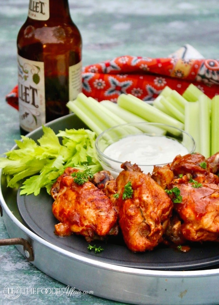 An appetizer with celery sticks, blue cheese dressing, and Instant Pot Chicken Wings with a BBQ sauce #chickenwings #InstantPot #appetizer #gameday | www.thefoodieaffair.com