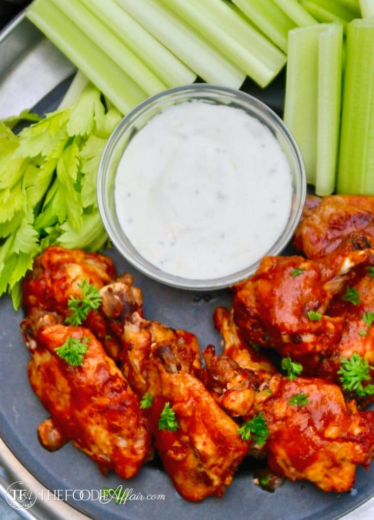 Homemade chicken wings made in an Instant Pot on a platter with celery and blue cheese dressing #bluecheese #appetizer #chickenwings | www.thefoodieaffair.com