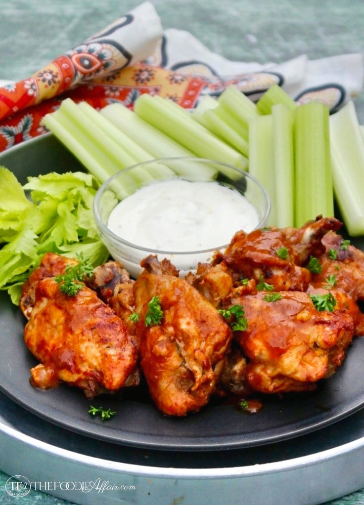 Instant Pot Chicken Wings on a black plate with celery and blue cheese dressing #instantpot #chickenwings #appetizer | www.thefoodieaffair.com