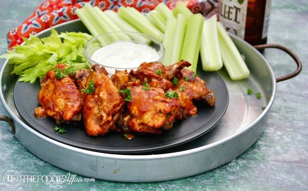 Instant Pot Chicken Wings appetizer coated in a BBQ sauce and served with celery sticks and blue cheese dressing with a beer #chickenwings #gameday #recipe #pressure cooker