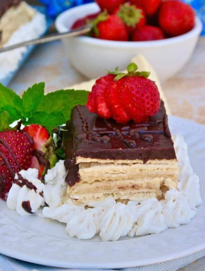 Slice of eclair dessert with strawberries on a white plate