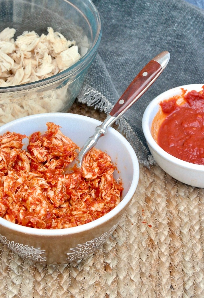 low carb bbq sauce over shredded chicken in a brown bowl