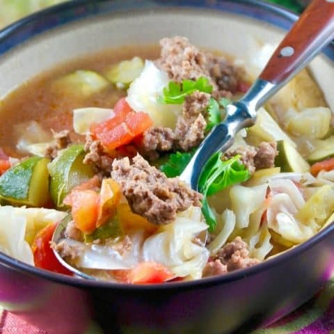 bowl of beef cabbage soup with a a wooden handle spoon