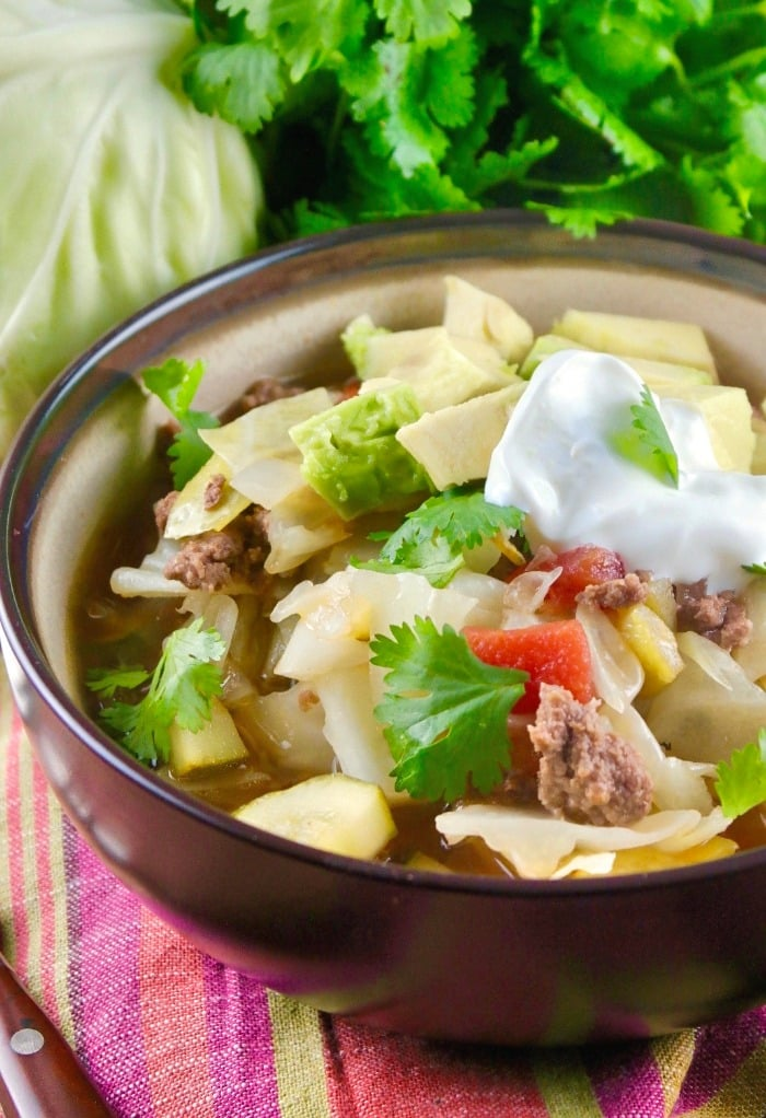 Brown bowl of beef cabbage soup topped with chunks of avocado
