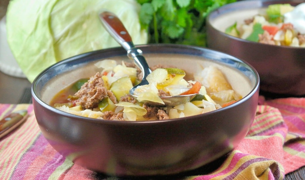 warm beef cabbage soup with a colorful napkin under the bowl