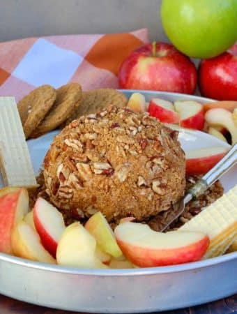 apple spice cream cheese ball on a platter with cookies and sliced apples