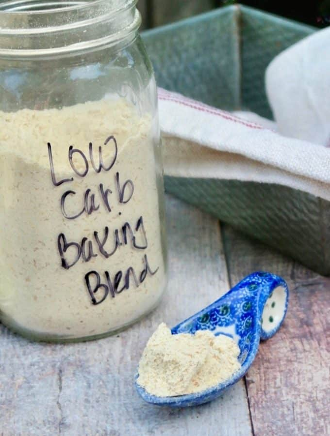 Clear mason jar of low carb baking mix with a blue spoon full of blend
