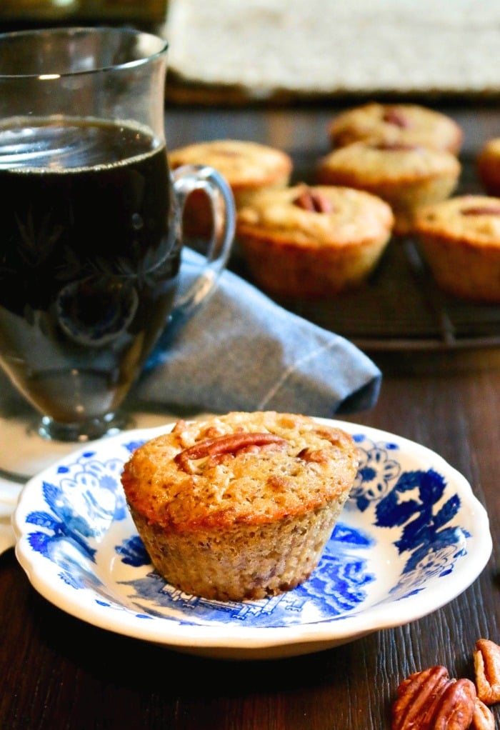 Pecan muffin on a blue and white plate with a cup of coffee on the side
