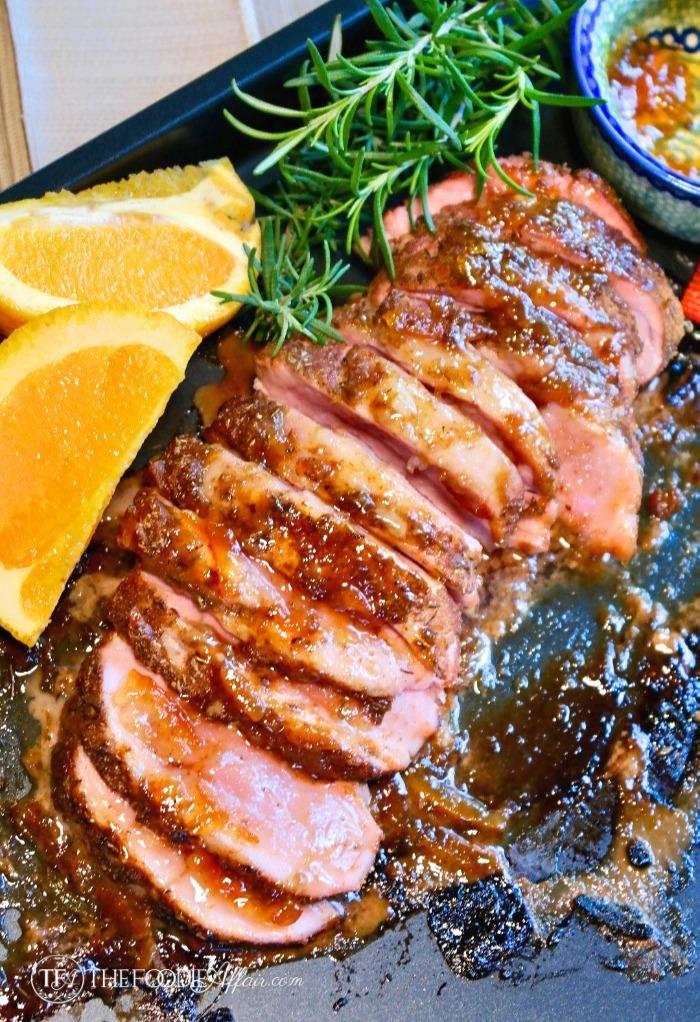 sliced baked pork tenderloin with orange marmalade on a baking sheet