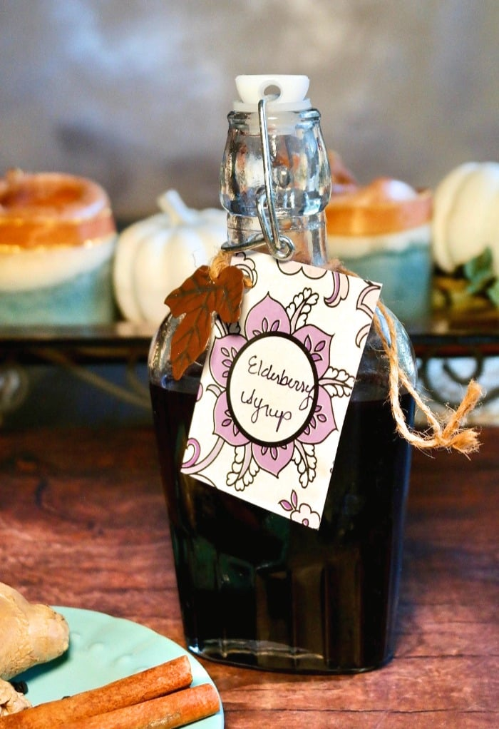 Homemade elderberry syrup recipe in a clear glass jar on a wooden table