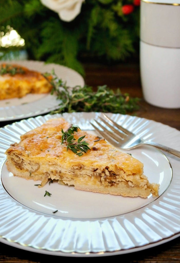 A slice of cheese and onion quiche topped with fresh thyme on a white and gray plate.