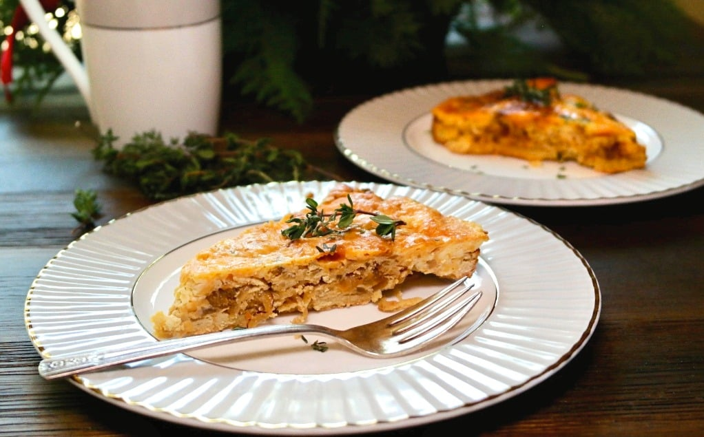 Two plates with cheese and onion quiche on a kitchen table