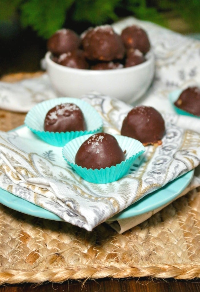 A plate of chocolate covered fat bombs on a white and silver napkin
