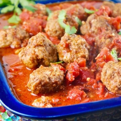 Slow cooked meatballs in a baking dish with a blue rim