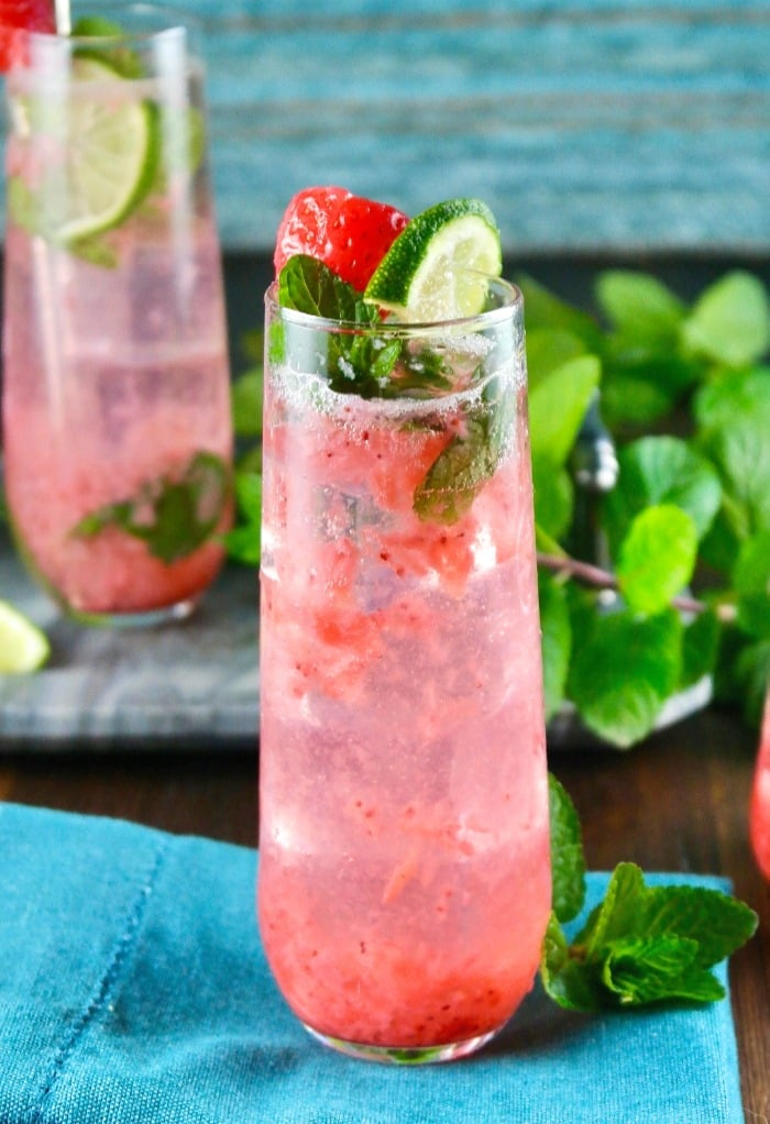 strawberry mojito cocktail in a tall glass with lime and mint