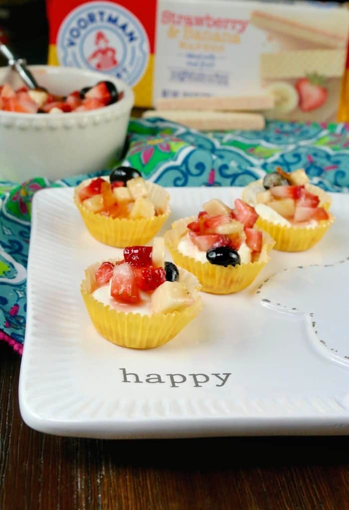 "mini cheesecake recipe in yellow cupcake liners on a white plate with the words ""happy"" written"