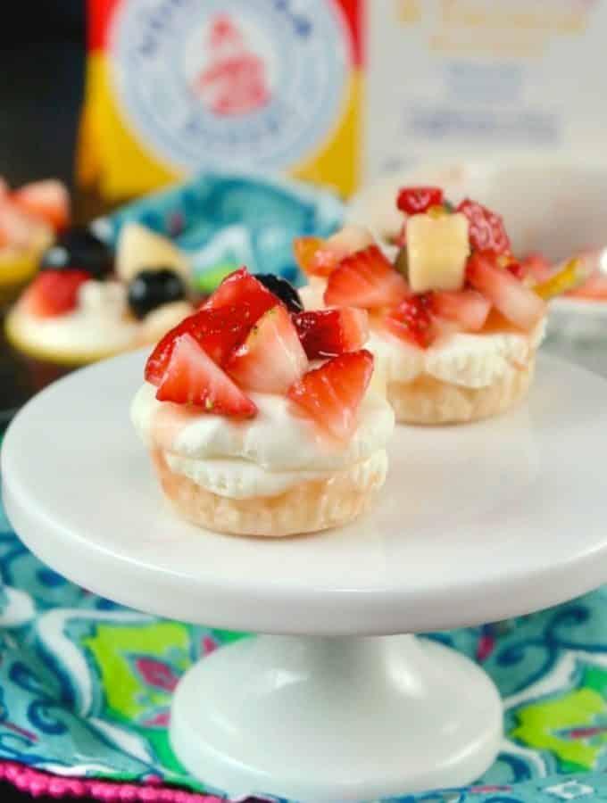 No Bake mini cheesecake recipe on a white small pedestal with floral napkin