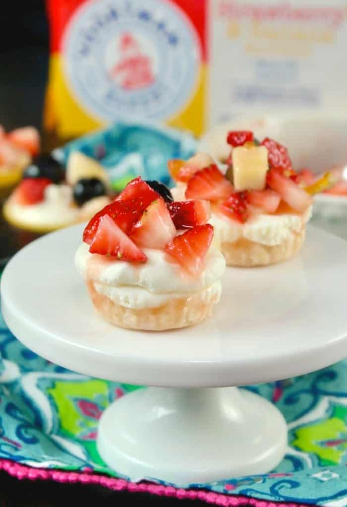 No Bake mini cheesecake recipe on a white small pedestal with floral napkin