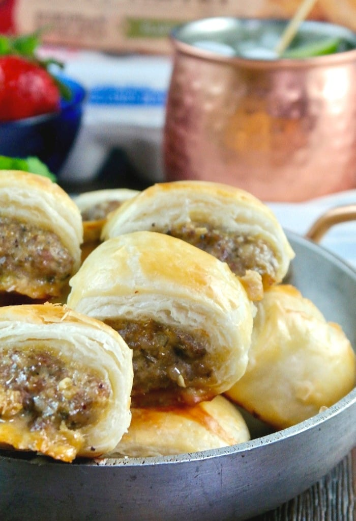 A silver bowl filled with sausage rolls in puff pastry