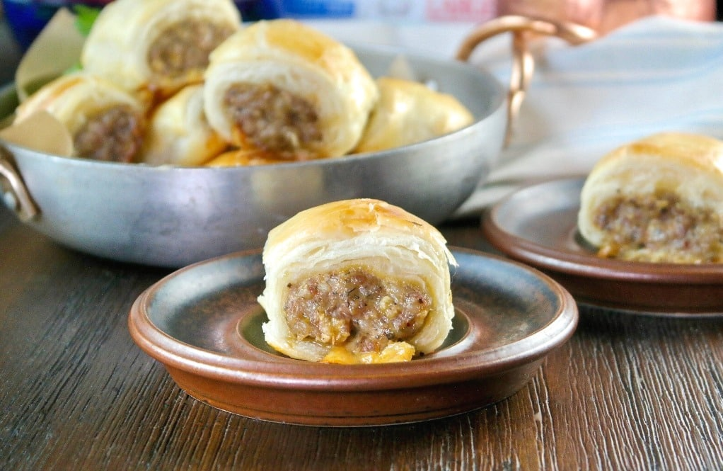 sausage roll in puff pastry on a brown appetizer plate