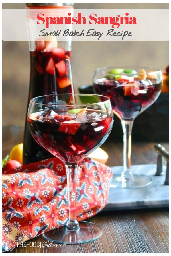 Red wine Spanish Sangria in a clear wine glass with a pitcher in the background