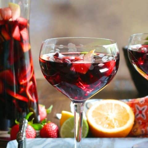 Clear wine glass filled with red Spanish sangria topped with fruit