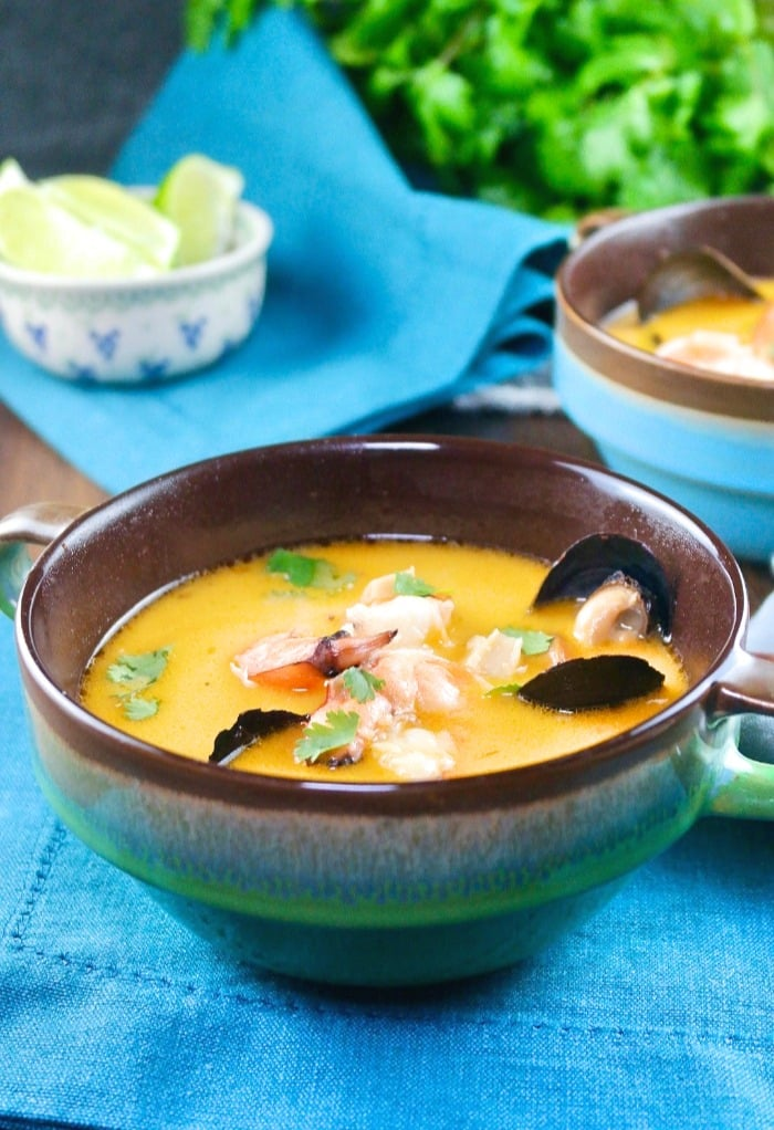Thai coconut soup with shrimp and muscles in a blue-green soup bowl