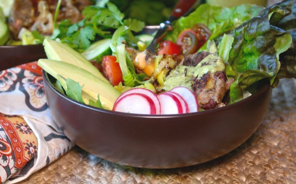 Brown bowl filled with salad, radish, and avocado slices