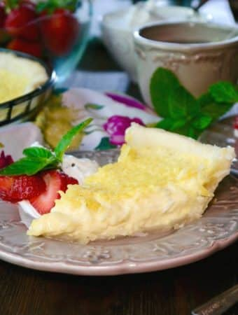 Slice of coconut custard pie on a tan plate with strawberries on the side