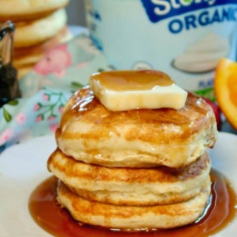 A stack of fluffy pancakes with butter and syrup