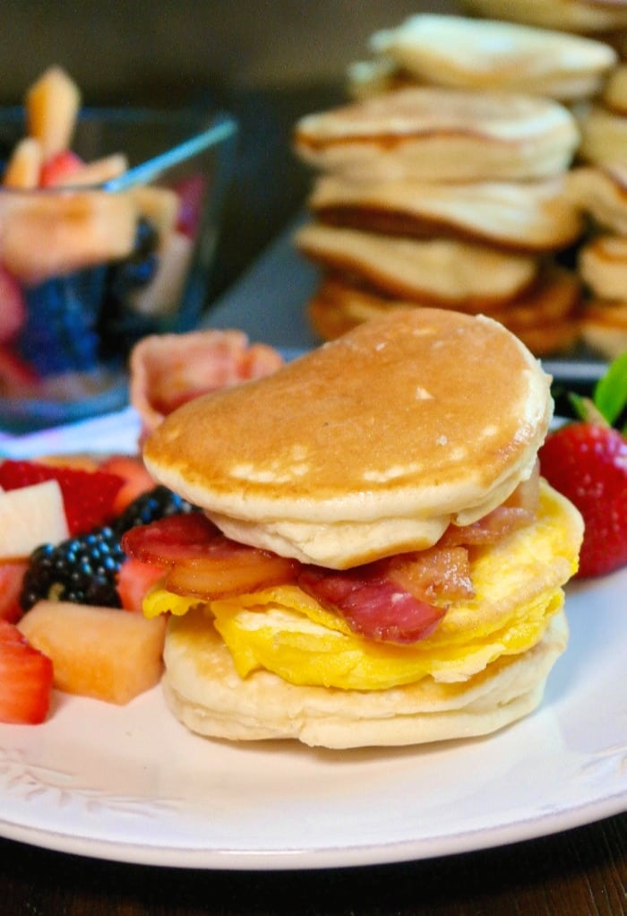 Fluffy pancakes between eggs and bacon