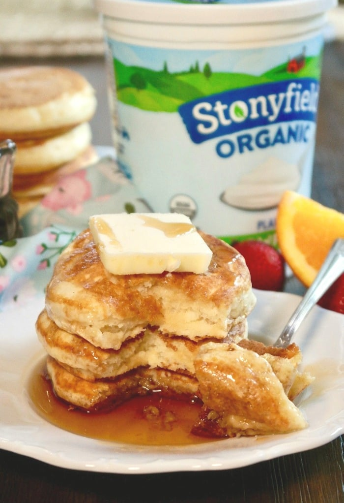 a stack of fluffy pancakes on a white plate