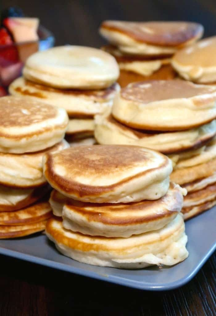 stacks of silver dollar size pancakes on a light blue tray