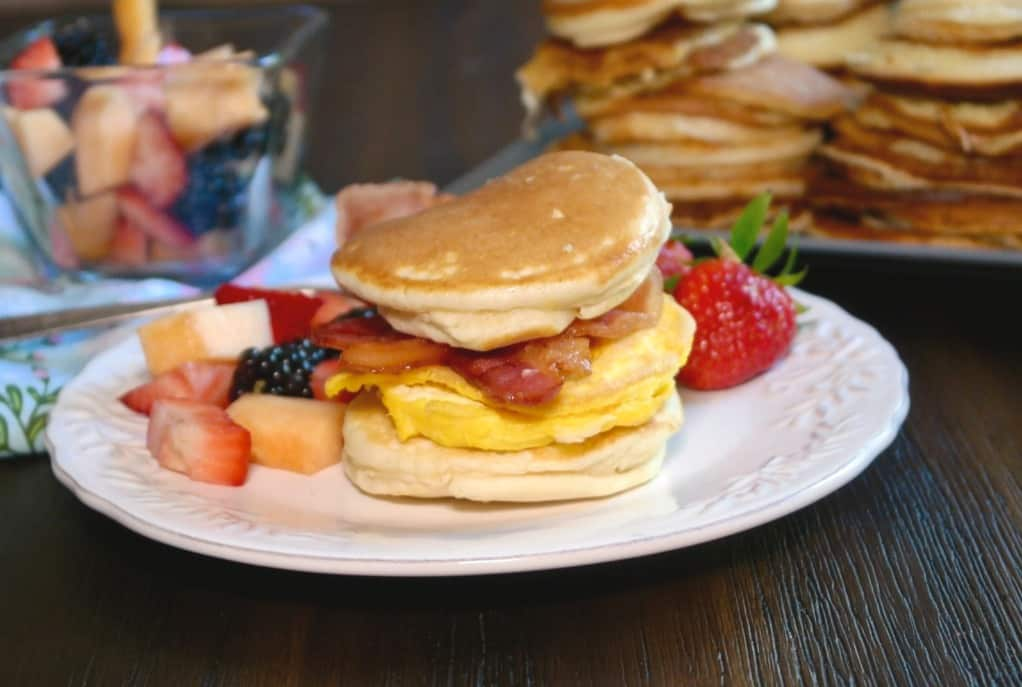 A white plate with fruit and hotcakes