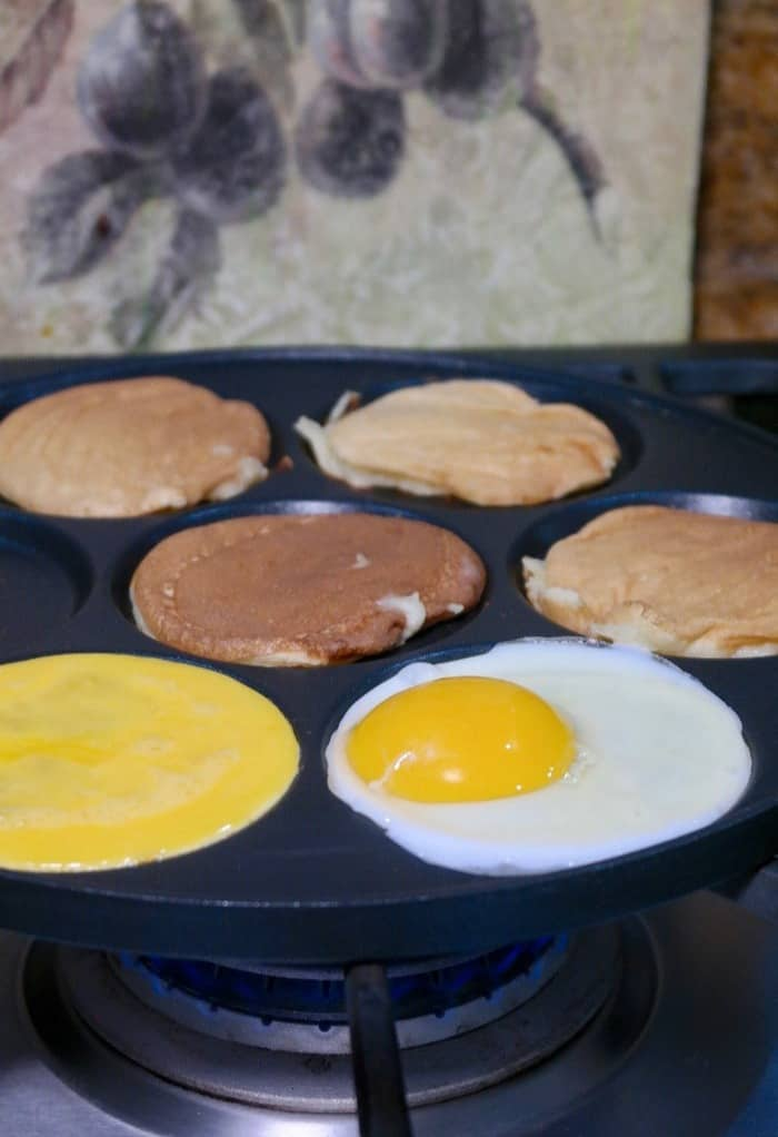 Eggs and pancakes on a black skillet