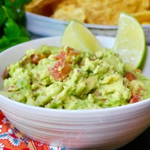 guacamole dip in a white bowl with slices of lime