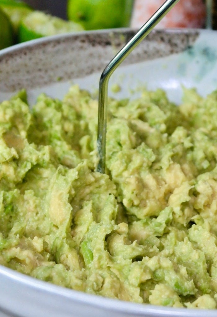 Mashed guacamole in a cream bowl for guacamole dip