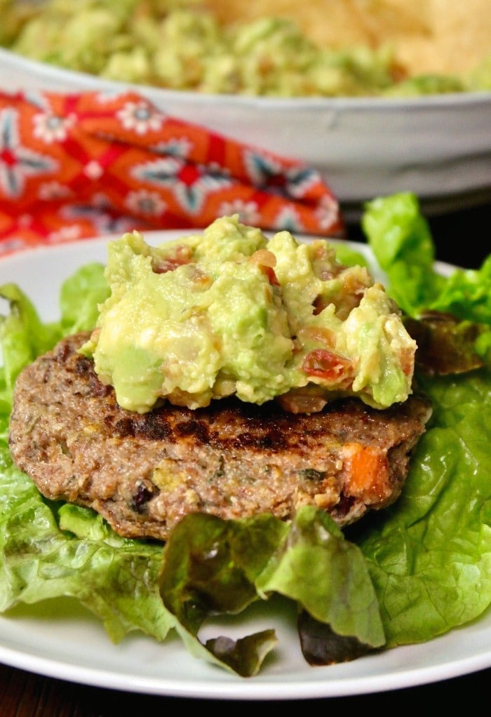 Bunless burger on a lettuce leaf topped with guacamole dip