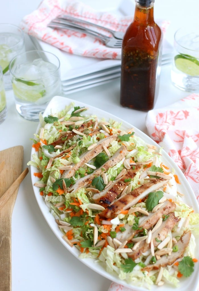 A grilled chicken salad recipe with  fresh ingredients like cabbage, carrots and green onions. Asian inspired flavors using ginger and roasted sesame seeds are added with the Asian salad dressing.
