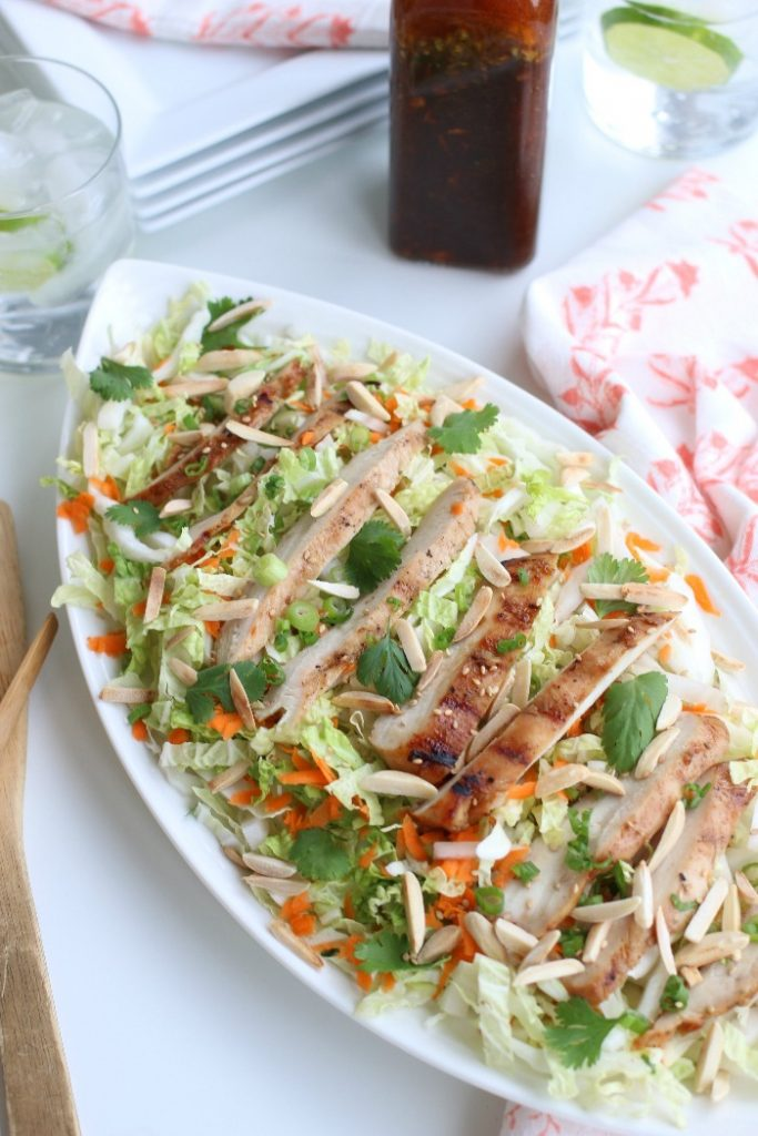 A grilled chicken salad recipe with cabbage, carrots and green onions. And a bottle of dressing on the side.