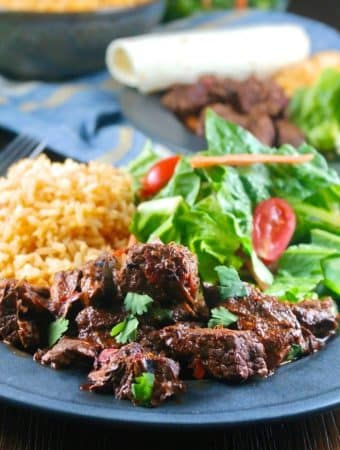 A black dinner plate filled with rice, salad and chili colorado con carne.