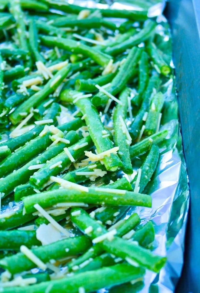 Fresh green beans on a foil lined baking sheet preparing for roasting.