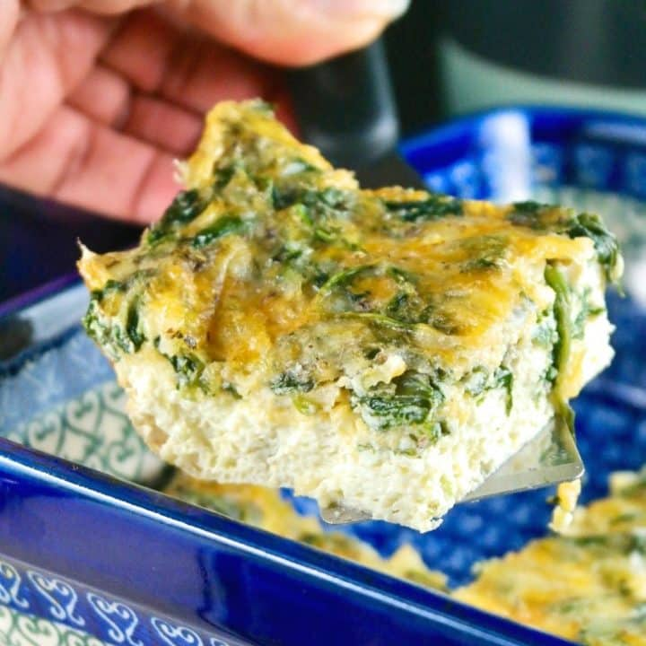 A slice of spinach egg bake in a blue casserole dish