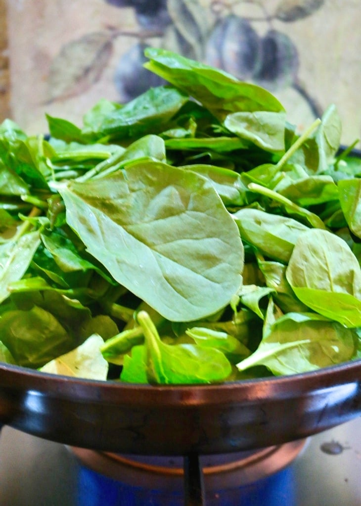 Fresh spinach sautéed in a skillet for spinach casserole.
