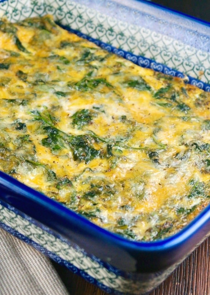 Spinach casserole with cheese and eggs in a blue Polish pottery casserole dish.