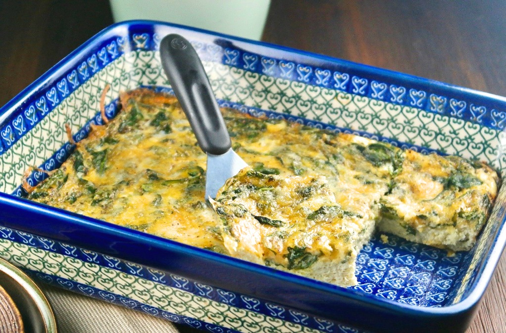breakfast casserole with spinach in a blue casserole dish