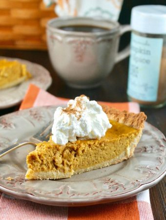Slice of low carb pumpkin pie on a tan plate